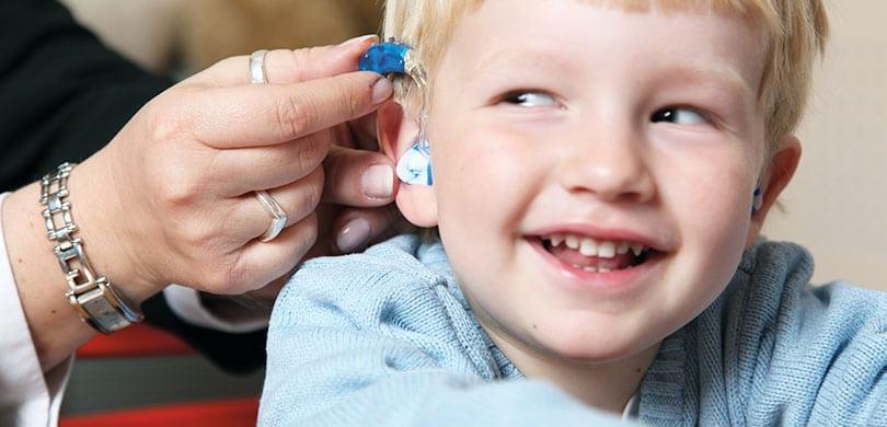 Garçon joyeux avec appareils auditifs
