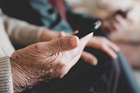 Couple âgé avec des appareils auditifs et un téléphone mobile