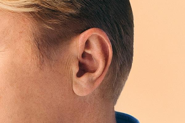 Ohr mit Hinter-dem-Ohr-HörgerätHörgerät