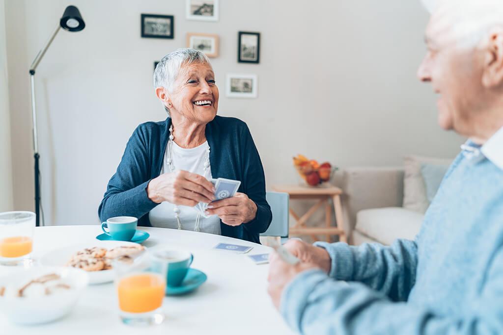 Älteres Paar beim Kartenspielen mit Hörgeräten