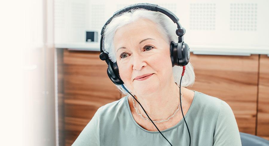 Frau mit Kopfhörern beim Hörtest bei Neuroth